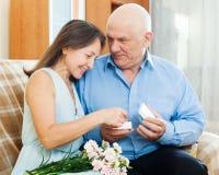 Glückliche reife Frau, die Juwel vom Ehemann schaut lizenzfreie stockfotos