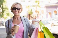 Glückliche reife Frau, die mit ihren Einkaufskäufen geht Stockbilder