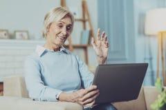 Glückliche reife Frau, die online in Verbindung steht lizenzfreies stockfoto