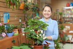 Glückliche reife Frau im Blumenspeicher Stockfotografie