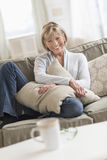 Glückliche reife Frau mit dem Kissen, das auf Sofa sitzt Lizenzfreie Stockbilder