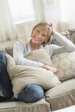 Glückliche reife Frau mit den Kissen, die auf Sofa sich entspannen Lizenzfreies Stockfoto