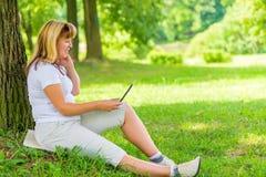 Glückliche reife Frau mit einem Laptop Stockfotos