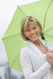Glückliche reife Frau mit grünem Regenschirm Stockbild