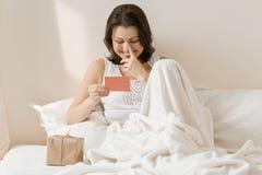 Glückliche reife Frau zu Hause im Bett mit Überraschungsgeschenklesegrußkarte Gefühl des Glückes, Freude, Überraschung stockfotografie