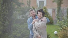 Glückliche reife Frauenstellung des Porträts im Garten vor dem großen Haus, erwachsener Enkel, der sie, Setzen umarmt stock video