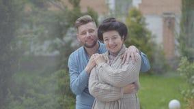 Glückliche reife Frauenstellung im Garten vor dem großen Haus, erwachsener Enkel, der sie, die Hand auf sie setzend umarmt stock video