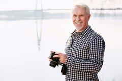 Glückliche reife Mannaufnahme mit Kamera stockbild