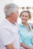 Glückliche reife Paare, die auf Bank in der Stadt sitzen Lizenzfreie Stockfotos