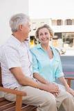 Glückliche reife Paare, die auf Bank in der Stadt sitzen Stockfotografie