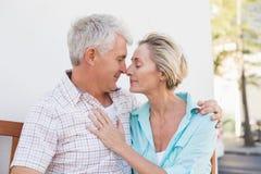 Glückliche reife Paare, die auf Bank in der Stadt sitzen Stockfotos