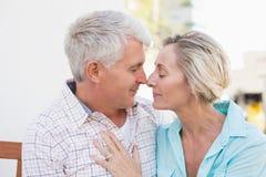Glückliche reife Paare, die auf Bank in der Stadt sitzen Stockbilder