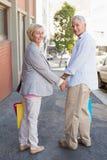 Glückliche reife Paare, die mit ihren Einkaufskäufen gehen Stockbild