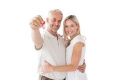 Glückliche reife Paare, die Schlüssel des neuen Hauses halten Lizenzfreie Stockfotos