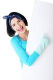 Glückliche Reinigungsfrau, die leeren Zeichenvorstand zeigt. Stockfoto