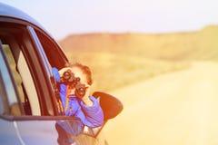 Glückliche Reise des kleinen Jungen mit dem Auto in den Bergen Stockbild