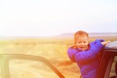 Glückliche Reise des kleinen Jungen mit dem Auto in den Bergen Stockfoto
