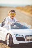 Glückliche Reise des kleinen Jungen mit dem Auto im Sommer Lizenzfreies Stockbild