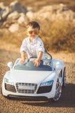 Glückliche Reise des kleinen Jungen mit dem Auto im Sommer Lizenzfreie Stockfotografie