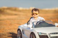 Glückliche Reise des kleinen Jungen mit dem Auto im Sommer Lizenzfreie Stockfotos