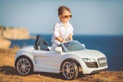 Glückliche Reise des kleinen Jungen mit dem Auto im Sommer Lizenzfreies Stockfoto