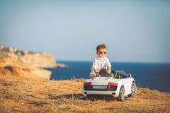 Glückliche Reise des kleinen Jungen mit dem Auto im Sommer Lizenzfreie Stockbilder