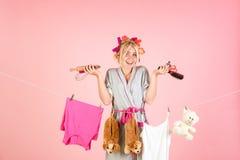 Glückliche Retro- Hausfrau Junge Mutter mit Schätzchen Weinlesehaushälterinfrau Mehrprozeßmutter Ausführung von verschiedenen Hau stockfotografie