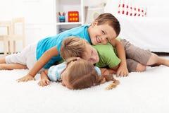 Glückliche ringende Kinder in einem Stapel Stockbilder