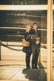Glückliche romantische attraktive junge Paare, die draußen lächeln und umarmen Reflexion im Spiegel, Shopfenster, Glas Stockbilder