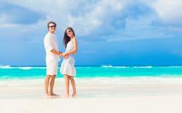 Glückliche romantische junge Paare, die am Strand gehen Lizenzfreie Stockfotografie