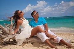 Glückliche romantische Paare, die Sonnenuntergang am Strand genießen Lizenzfreie Stockfotos