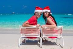Glückliche romantische Paare in roter Santa Hats an Lizenzfreie Stockfotos