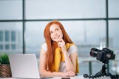 Glückliche Rothaarige weiblicher Blogger mit Laptop denken an neues Thema für vlog Lizenzfreies Stockbild
