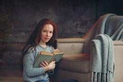 Glückliche Rothaarigefrau, die sich zu Hause im gemütlichen Winter- oder Herbstwochenende mit Buch entspannt stockfotografie