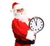 Glückliche Sankt in den Brillen zeigend auf die Uhr, die fünf Minuten zeigt Stockbild