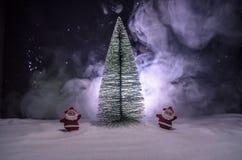 Glückliche Santa Claus Doll auf Weihnachtszeit mit Baum und Schnee Bunter bokeh Hintergrund Modellfeige Weihnachtsmanns und der f Stockbilder