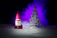 Glückliche Santa Claus Doll auf Weihnachtszeit mit Baum und Schnee Bunter bokeh Hintergrund Modellfeige Weihnachtsmanns und der f Stockbild