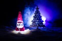 Glückliche Santa Claus Doll auf Weihnachtszeit mit Baum und Schnee Bunter bokeh Hintergrund Modellfeige Weihnachtsmanns und der f Lizenzfreies Stockbild