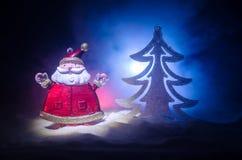 Glückliche Santa Claus Doll auf Weihnachtszeit mit Baum und Schnee Bunter bokeh Hintergrund Modellfeige Weihnachtsmanns und der f Lizenzfreies Stockfoto
