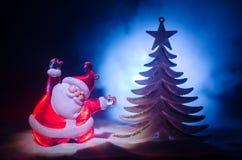 Glückliche Santa Claus Doll auf Weihnachtszeit mit Baum und Schnee Bunter bokeh Hintergrund Modellfeige Weihnachtsmanns und der f Lizenzfreie Stockbilder