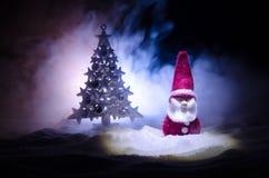 Glückliche Santa Claus Doll auf Weihnachtszeit mit Baum und Schnee Bunter bokeh Hintergrund Modellfeige Weihnachtsmanns und der f Stockfoto