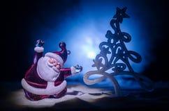 Glückliche Santa Claus Doll auf Weihnachtszeit mit Baum und Schnee Bunter bokeh Hintergrund Modellfeige Weihnachtsmanns und der f Stockfotografie