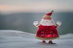 Glückliche Santa Claus Doll auf Weihnachtszeit mit Baum und Schnee Unscharfer Hintergrund im Freien Modell-FI Weihnachtsmanns und Lizenzfreie Stockfotografie