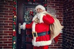 Glückliche Santa Claus kommt mit Geschenk auf großer Tasche nachts in an stockfotografie