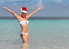 Glückliche Santa Girl auf tropischem Strand. Schöne blonde junge Frau Stockbild