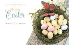 Glückliche schäbige schicke Tabelle Ostern mit gesprenkelten Vogeleiern und -schmetterling im Nest Lizenzfreie Stockbilder