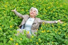 Glückliche schöne ältere Frau, die im Frühjahr auf einer Lichtung von gelben Blumen sitzt Lizenzfreies Stockbild