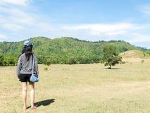 Glückliche schöne Asiatin mit Hut und Tasche bereit, Ferien an der Ecke mit Landschafts-Berg im Hintergrund zu beginnen lizenzfreie stockbilder