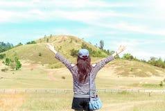Glückliche schöne Asiatin mit Hut und Tasche streckte ihre Arme aus, die bereit sind, zu beginnen Ferien mit Landschafts-Berg im  lizenzfreie stockbilder