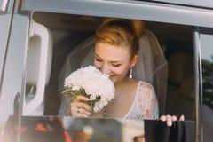 Glückliche schöne blonde Braut schnüffelt Blumen im Auto Stockfotografie